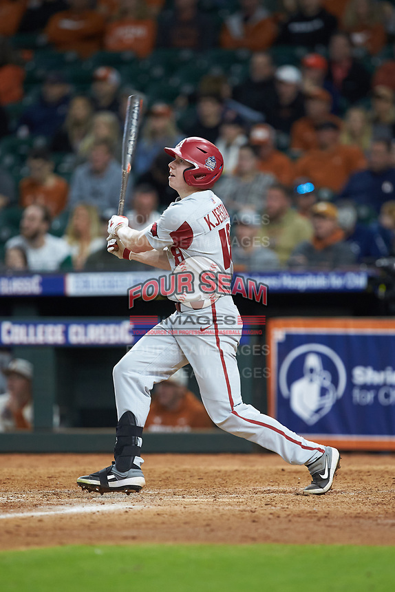 Heston Kjerstad (18) of the Arkansas Razorbacks follows through on his swing against the Texas Longhorns in game six of the 2020 Shriners Hospitals for Children College Classic at Minute Maid Park on February 28, 2020 in Houston, Texas. The Longhorns defeated the Razorbacks 8-7. (Brian Westerholt/Four Seam Images)