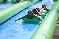 NWA Democrat-Gazette/J.T. WAMPLER Several thousand people turned out for a 1,000 foot long water slide on Dickson St. in Fayetteville Sunday August 30, 2015. The water slide was brought to Fayetteville by Slide the City, a company based in Salt Lake City. Part of the event's proceeds will benefit Soldier On Service Dogs, a nonprofit organization that raises, trains and gives away service dogs to veterans who have post-traumatic stress disorder or traumatic brain injuries.