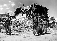 ROK military police pose before the ruins of a devastated building in Pohang.  Most buildings that housed red troops were destroyed.  October 17, 1950. (Navy)<br /> NARA FILE #:  080-G-420652<br /> WAR &amp; CONFLICT BOOK #:  1502