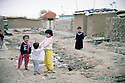 Irak 2000.Erbil: Des enfants de familles déplacées jouent dans les rues d'un ancien camp militaire irakien, lieu de leur résidence.     Iraq 2000.Children playing in a former Iraqi military camp