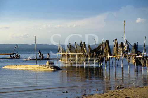 Itaparica, Brazil. Fishing nets draped over poles above the water in the sun with children playing in the water.