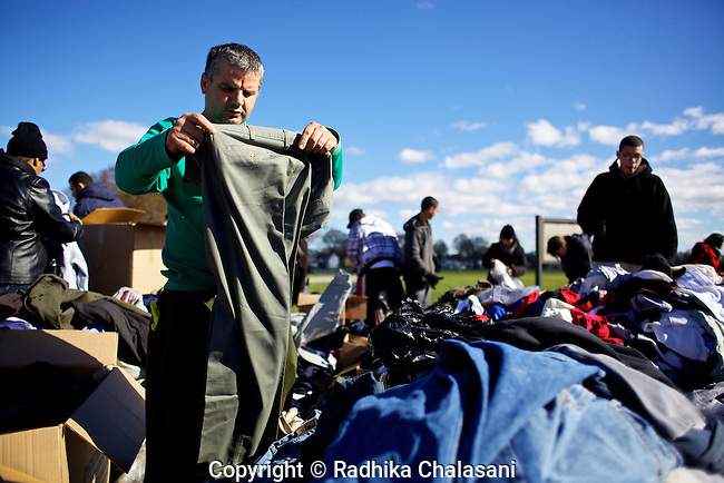 NEW DORP BEACH,NEW YORK-NOVEMBER 3: Sabre Elia, staying with friends after losing his home, looks through clothing donations in the parking lot at New Dorp High School in the aftermath of Hurricane Sandy November 3, 2012 in the Staten Island borough of New York City. Staten Island saw an influx of volunteers and donations today to help devastated residents recover from the storm.