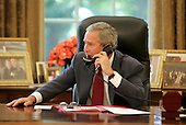 Washington, D.C. - July 23, 2006 -- United States President George W. Bush offers his congratulations to Tour de France winner Floyd Landis during a phone call from the Oval Office, Sunday, July 23, 2006. .Credit: Kimberlee Hewitt-White House via CNP.