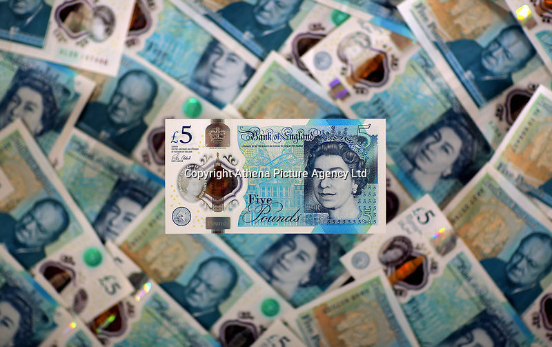 A £5 note resting on a bed of new ones<br />