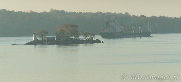 A freighter passes Crossover Island Lighthouse on a placid St. Lawrence River, one  autumn morning in the1000 Islands of New York State.