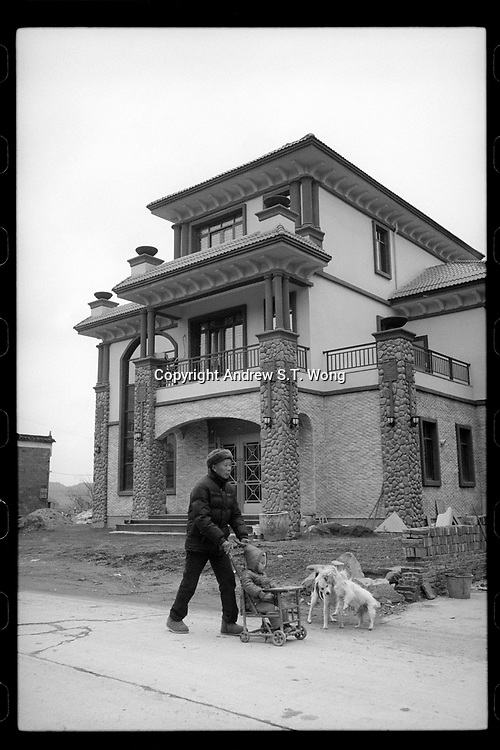 A villager pushes his grandson past a newly built house in Poyang county at Poyang Lake, Jiangxi Province, November 2017. Poyang Lake, located in the north of Jiangxi Province, is the largest freshwater lake in China. It fluctuates dramatically between wet and dry seasons, from 3,500 square kilometres down to about 200 square kilometres. The lake provides a habitat for half a million migratory birds.