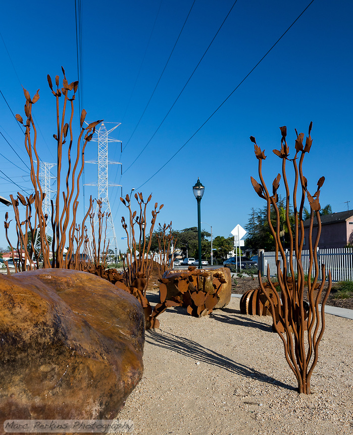 A sculpture garden made out of rusted metal parts in a desert hteme: ocotillos, barrel cacti, opuntia, and rust-colored rocks.