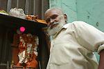 Man beside shrine to Hanuman, the monkey god,in the Paharganj district of New Delhi, India.