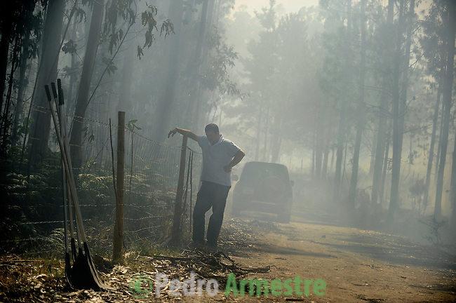 A man gestures around the fire area in Boiro, on August 15, 2010, near A Coruña. Pedro ARMESTRE