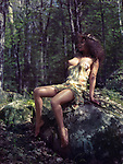 Beautiful sexy half nude woman sitting on rocks in a forest in a seductive sensual pose with a sheer dress revealing her naked breast and legs
