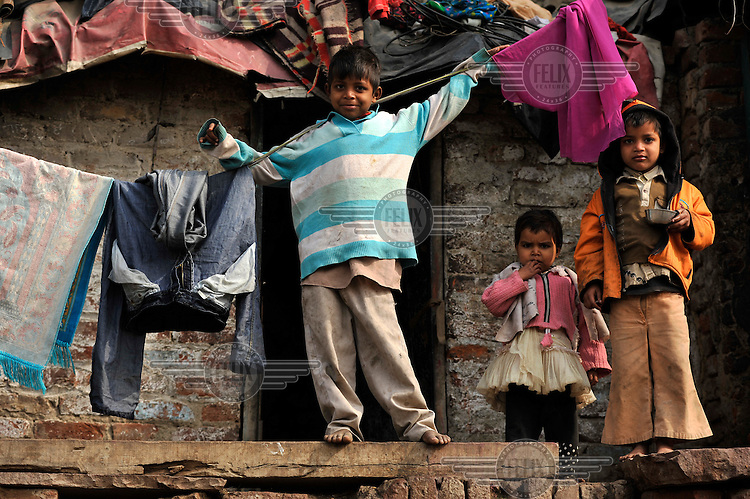 Children stand on a wall in a slum in the area of Nizamuddin East.