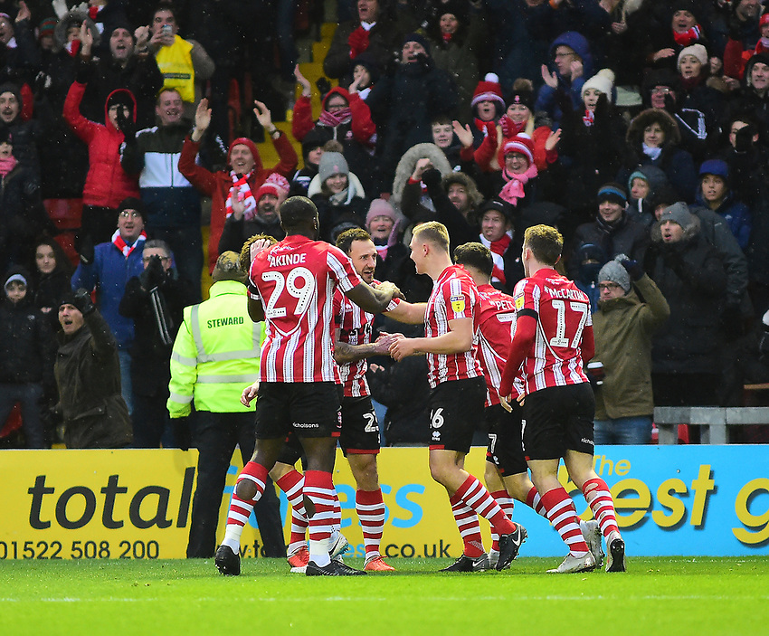 Lincoln City's Harry Anderson celebrates scoring the opening goal with team-mates<br /> <br /> Photographer Andrew Vaughan/CameraSport<br /> <br /> The EFL Sky Bet League Two - Saturday 15th December 2018 - Lincoln City v Morecambe - Sincil Bank - Lincoln<br /> <br /> World Copyright © 2018 CameraSport. All rights reserved. 43 Linden Ave. Countesthorpe. Leicester. England. LE8 5PG - Tel: +44 (0) 116 277 4147 - admin@camerasport.com - www.camerasport.com