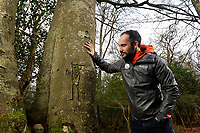 BNPS.co.uk (01202 558833)<br /> Pic: ZacharyCulpin/BNPS<br /> <br /> Pictured: Lawrence Shaw, archaeologist at the New Forest NPA with graffiti of a man with his hands in the air. The graffiti is thought to be around 100 years old as the tree gets bigger the carving warps around the tree.<br /> <br /> Fascinating ancient graffiti which was carved into the trees of the New Forest centuries ago is being formally recorded for the first time.Initials, dates, pictures, poems and royal marks which vary in size from 4ins to 2ft can be found throughout the national park in Hampshire.There are also various examples on display of concentric circles, known as 'witches marks', which were carved to ward off evil spirits.In total, hundreds of examples of 'tree graffiti' are being documented in a new database set up by the New Forest National Park Authority.