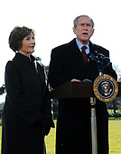United States President George W. Bush, with First Lady Laura Bush, speaks about the terrorist attacks on Mumbai, India after arriving at the White House from Camp David, in Washington on November 29, 2008.<br /> Credit: Alexis C. Glenn / Pool via CNP
