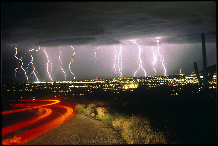 USA_SCI_LIG_001_nxs.Summer lightning storm over Tucson, Arizona from Tumamoc Hill with Saguaro cactus. Storms erupt regularly during Arizona summers due to the moist air that flows in from the Gulf of California then collides with nearby mountains and is forced upward, where it condenses into thunderclouds. ..Lightning occurs when a large electrical charge builds up in a cloud, probably due to the friction of water and ice particles. The charge induces an opposite charge on the ground, and a few leader electrons travel to the ground. When one makes contact, there is a huge backflow of energy up the path of the electron. This produces a bright flash of light, and temperatures of up to 30,000 degrees Celsius. Tucson, Arizona, USA. (1992) .In this photograph a 2-minute time exposure captures multiple lightning strikes during an early evening thunderstorm as well as the tail lights of the photographer's rental car driven through the scene to add color. Photographed from Tumamoc Hill, Tucson, Arizona. .