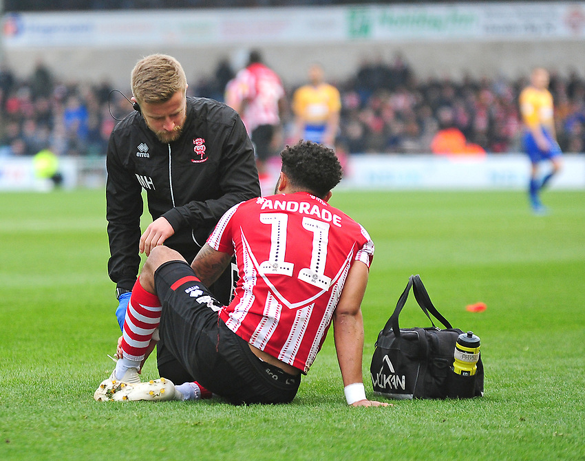 Lincoln City's head of sports science and medicine Mike Hine treats Lincoln City's Bruno Andrade<br /> <br /> Photographer Andrew Vaughan/CameraSport<br /> <br /> The EFL Sky Bet League Two - Lincoln City v Mansfield Town - Saturday 24th November 2018 - Sincil Bank - Lincoln<br /> <br /> World Copyright © 2018 CameraSport. All rights reserved. 43 Linden Ave. Countesthorpe. Leicester. England. LE8 5PG - Tel: +44 (0) 116 277 4147 - admin@camerasport.com - www.camerasport.com