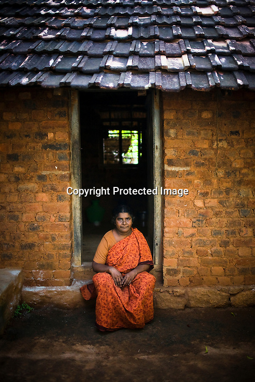 49 years old Joyce took a loan of Rs. 52,000 (1051$) from the bank to build her two room apartment. she pays mortgage of Rs. 500 per month. She lives in her new apartment with her husband and two daughters. Here she poses in front of her old hut. She shells raw cashews in cashew processing factory in Prassala, Kanyakumari district in Tamil Nadu, India.. .An estimated number of 500,000 women process cashews for a living in Tamil Nadu and Kerela. 2 million people are employed by cashew industry across India making it the world's biggest exporter of shelled cashews. .The working conditions in these processing units are way below industry standards and violates the basic rights. Wages are as low as Rs. 50 (US $1) per day. The problems for these women is not restricted to low wages. Many women are being injured by their jobs as the factory owners cut corners with health and safety. Oil released during the cashew shelling process is highly caustic, leading to common cases of dermatitis, blistering and discolouration of workers' skin. Women working in these units suffer from pains in their leg muscles, backs and knee joints after squatting positions on mud or concrete floors. It is very rare to find tables and chairs provided on shelling duty..Cashew workers' main concern is to increase their earnings and provide better working conditions. .Photo: Sanjit Das