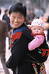 Woman with baby in cloth sling on her back; smiles for viewer; street portrait in Zhongxian, China, Asia; 041903