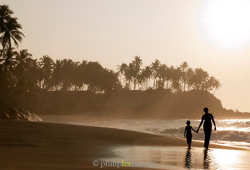 Mother and daughter walking along a sandy beach at sunrise in Tangalle, Sri Lanka