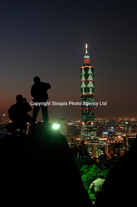 Two photographers stand silhouetted against the night sky before Taipei 101 Tower in Taipei, Taiwan. Completed in December 2004, the 508m-high skyscraper is the world's tallest building..