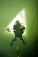 Ice diver under the ice in Northern Russia in the White Sea.