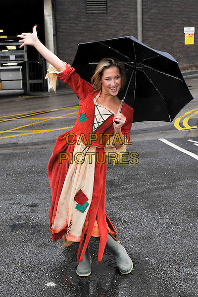 GIMMA BISSIX  .'Cinderella' photocall at the Fairfield Halls in Croydon, London, England..October 2010.panto pantomime play stage costume red dress full length rags yellow wellington wellies boots umbrella rain raining.CAP/MAR.© Martin Harris/Capital Pictures.