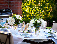 A table is laid for lunch outdoors in the sunshine.