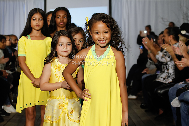 Child models walk runway in outfits from the Almond Eyez Designs collection, during the KidFash Magazine runway show in Brooklyn, New York on Nov 4, 2017.