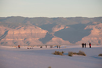People walk among the sand dunes at White Sands National Monument near Alamogordo, New Mexico, USA, on Sat., Dec. 30, 2017.
