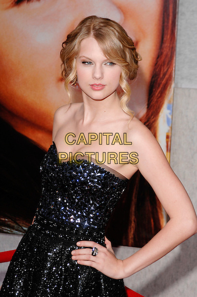 "TAYLOR SWIFT.The world premiere of ""Hannah Montana The Movie"" at El Capitan Theatre in Hollywood, California, USA.  .April 2nd, 2009.half length dress strapless black sequined sequins beads beaded blue hand on hip ring .CAP/ROT.©Lee Roth/Roth Stock/Capital Pictures"