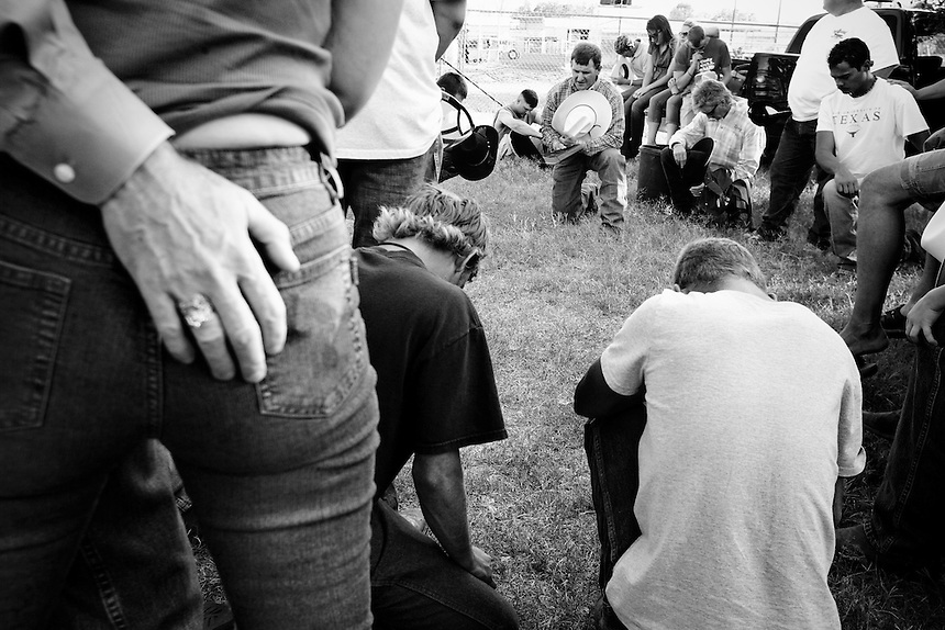 Cowboy prayer before the rodeo begins in Llano, Texas.  June 7, 2008.