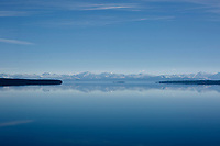 Mountains are reflected in a calm Yellowstone Lake as morning haze hangs near the waterline in Yellowstone National Park, Wyoming on Tuesday, May 23, 2017. (Photo by James Brosher)