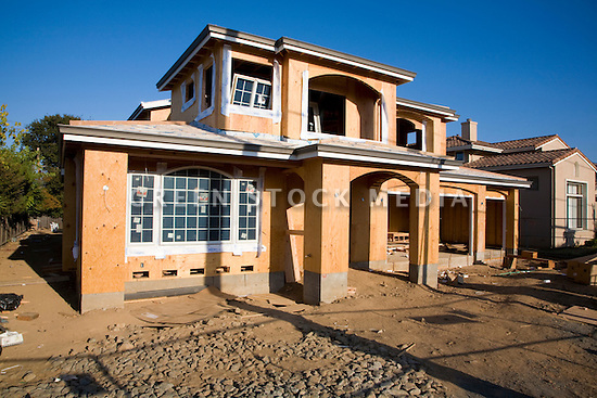 A front view of a large two-story conventional wood frame house under construction. Large amounts of wood and other raw materials are being used to build this new house on a lot where a small single-story home was demolished. Cupertino, California, USA