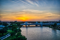 We captured this fabulous aerial sunset over the brazos river in Waco Texas  with the new stay bridge with the lights on.  The sky was full of this soft orange glow from the sunset against the blue lights on the bridge with the brazos river below all capture from above.  This section of IH35 is a stay bridge with these wonderful led lights that constantly slowly change colors.  We thought the wonderful sunset was a great backdrop against the blue lights on the bridge in this image.  All capture from the air with our drone.  The IH 35 highway through Waco is also called the is called the Jack Kultgen Freeway named after a civic leader and philanthropist who did a lot of work for charities in Waco for six decades.