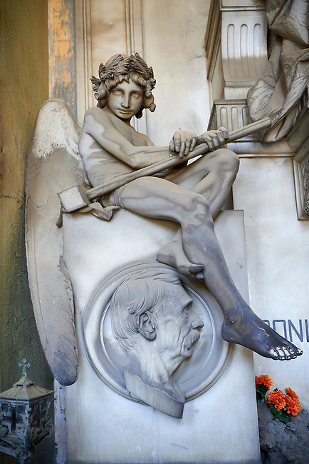 Picture and image of a stone sculpture of an angel by Sculptor V. Lavezzari 1897 on the Repetto tomb. The angel is holding a club and has a vacant look in its eyes giving it a mysterious sense of death. Section A, no 52, The monumental tombs of the Staglieno Monumental Cemetery, Genoa, Italy