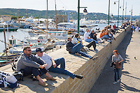 "France, FRA, Département Var, Saint-Tropez, 2008Oct04: Tourists sit on a wall in the port of Saint-Tropez at the Cote d'Azur / Provence watching the boats during the regatta ""Les Voiles de Saint-Tropez""."