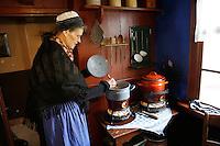 Enkhuizen. Huisje uit Urk in het Zuiderzeemuseum. Vrouw kookt eten op een oud petroleumstel