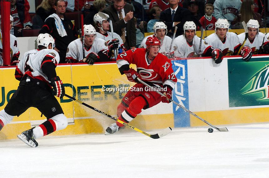 Ottawa Senators' Chris Phillips (4) defends the Carolina Hurricanes' Eric Staal (12) during their game Tuesday, Nov. 22, 2005 in Raleigh, NC. Ottawa won 5-3.