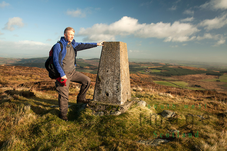 Hill walker at trig point on Lotus Hill looking across Loch Arthur to Mabie Forest and Dumfries.