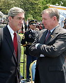 Washington, DC - May 15, 2004 -- United States Attorney General John Ashcroft, right, shares some thoughts with Federal Bureau of Investigation (FBI) Director Robert Mueller, left, after President George W. Bush made remarks at the Annual Peace Officers' Memorial Service on the West Lawn of the United States Capitol in Washington, D.C. on May 15, 2004.  The service, sponsored by the Fraternal Order of Police (FOP), is held annually on May 15 to honor those who gave their lives during the previous year and to honor their families.  The service remembers the sacrifice of the more than 15,000 officers who have been killed in the line of duty since 1794.<br /> Credit: Ron Sachs / CNP<br /> (RESTRICTION: NO New York or New Jersey Newspapers or newspapers within a 75 mile radius of New York City)