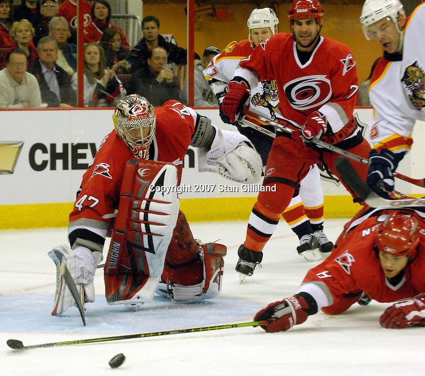 Carolina Hurricanes' Tim Gleason, right, reaches for a puck following a save by teammate John Grahame as Niclas Wallin (7) watches during a game against the Florida Panthers Tuesday, March 13, 2007 at the RBC Center in Raleigh, NC. Carolina won 3-1.