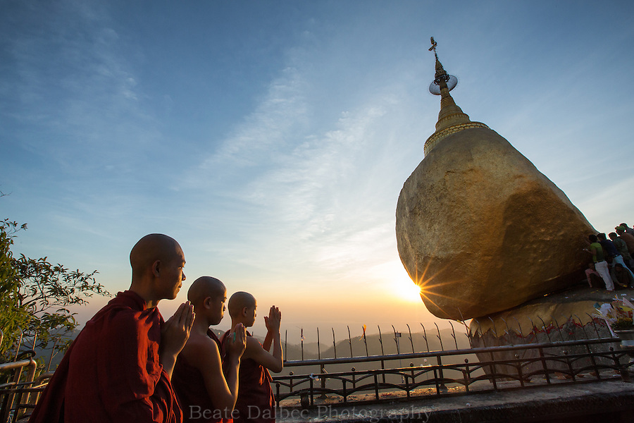 Monks praying at the Golden Rock, Myanmar, at sunset
