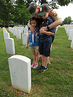 NWA Democrat-Gazette/ANDY SHUPE<br /> Cody Villar (center) of Fayetteville holds his daughter, Cora, 7; and son, Joseph, 9; Saturday, May 27, 2017, as they pause to remember the children's grandfather, Joseph Arthur Davis, at his grave marker in the Fayetteville National Cemetery. Residents were invited to place flags at each marker as a part of the cemetery's observance of Memorial Day. Gov. Asa Hutchinson will speak in honor of the cemetery's 150th Anniversary at 10 a.m. Monday during the facility's annual Memorial Day ceremony. Visit nwadg.com/photos to see more photographs from the morning.