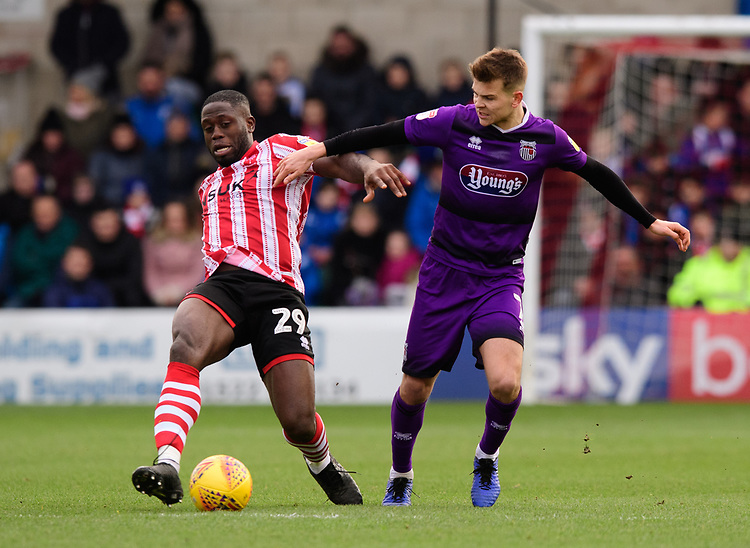 Lincoln City's John Akinde vies for possession with Grimsby Town's Jake Hessenthaler<br /> <br /> Photographer Chris Vaughan/CameraSport<br /> <br /> The EFL Sky Bet League Two - Lincoln City v Grimsby Town - Saturday 19 January 2019 - Sincil Bank - Lincoln<br /> <br /> World Copyright © 2019 CameraSport. All rights reserved. 43 Linden Ave. Countesthorpe. Leicester. England. LE8 5PG - Tel: +44 (0) 116 277 4147 - admin@camerasport.com - www.camerasport.com