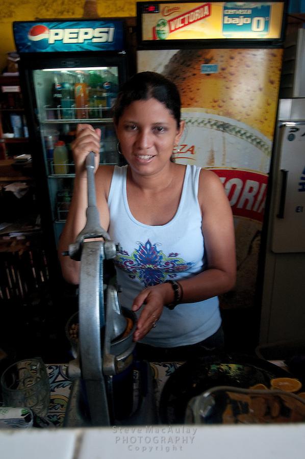 Woman squeezing fresh oranges for juice, San Juan Del Sur, Nicaragua
