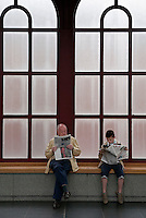 Belgium, Antwerp: Adult and child reading newspapers at the Centraal Station