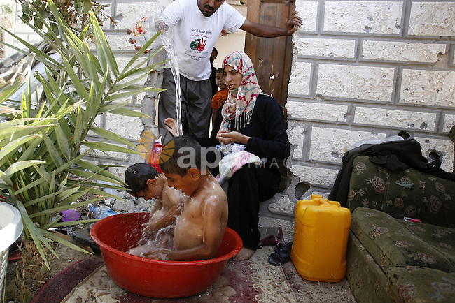 """A Palestinian couple bathes their childre at a destroyed house in Khan Yunis in the southern Gaza Strip on September 11, 2014. Israel's deputy foreign minister,Tzahi Hanegbi , warned that Hamas was likely to resume """"violence"""" if it feels it has made no political gains from upcoming talks in Cairo. Photo by Abed Rahim Khatib"""