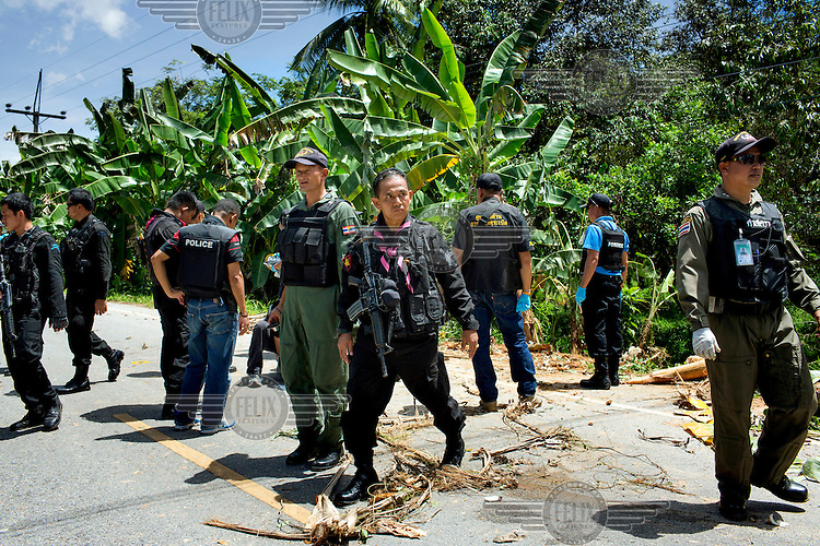 Thai Army Rangers, Forensic Police and EOD (Explosive Ordinance Disposal) specialists investigate the site of a bomb that had recently gone off killing one Ranger and wounding two others in Kradoh Village near Pattani. /Felix Features