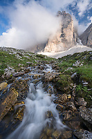 Tre Cimi formation is surrounded by clouds above a pure flowing stream, Dolomite Range, Italy.