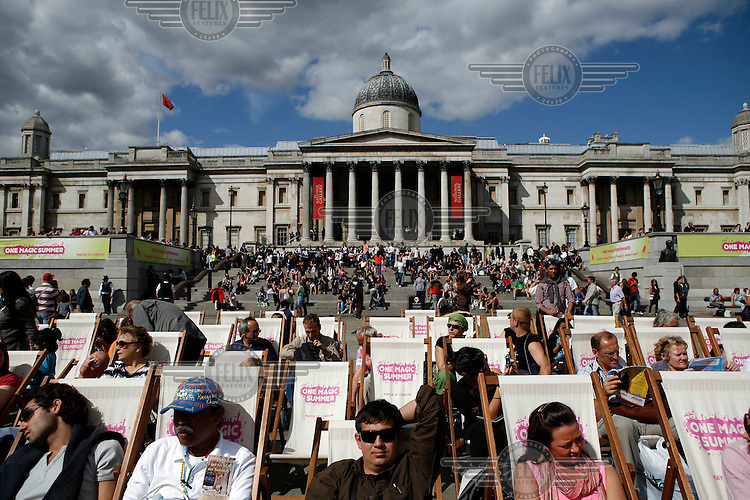People sun bathe on deckchairs in front of the National Gallery on Trafalgar Square, London.